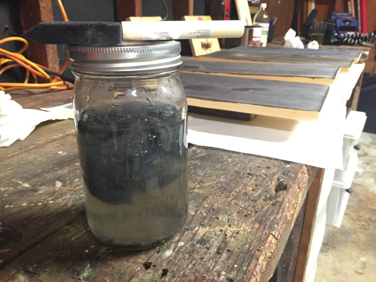 oxidation solution of steel wool and vinegar sitting on a workbench