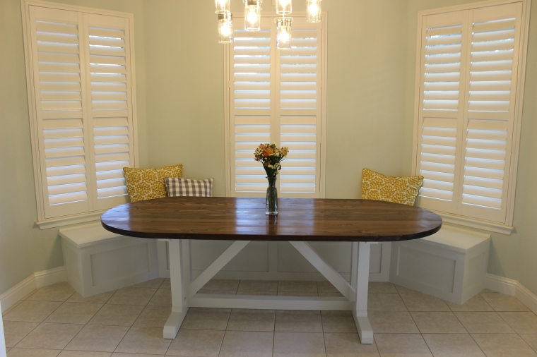 wide view of racetrack-shaped dining table in nook