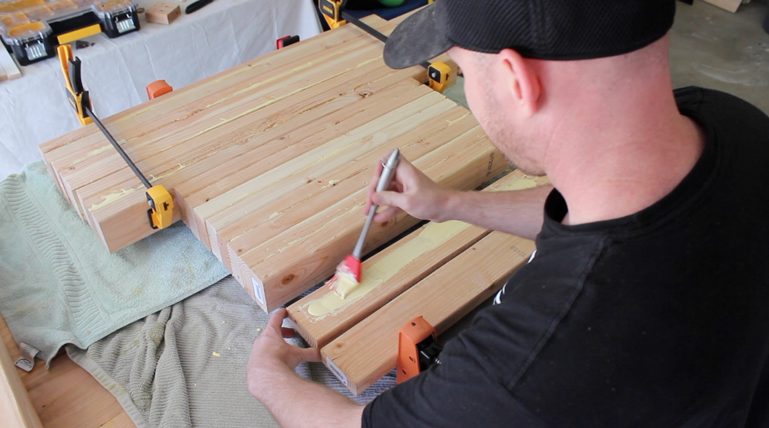 gluing together 2 by 4 boards for the table legs