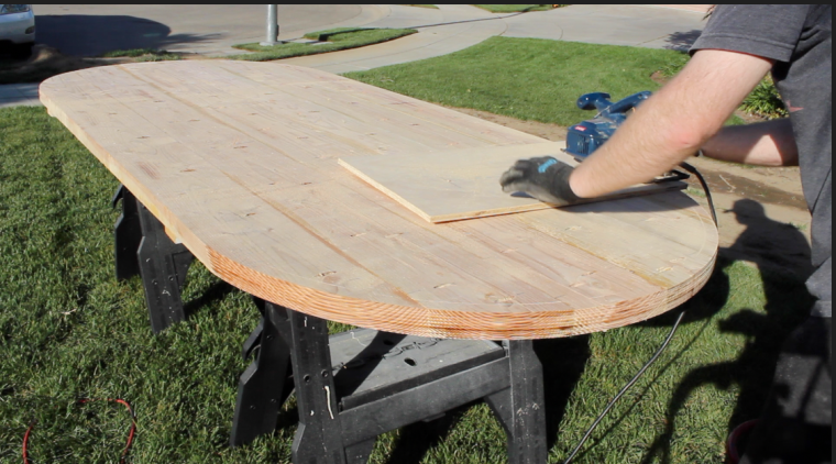 using a circular saw to make a half-circle cut in the dining table top