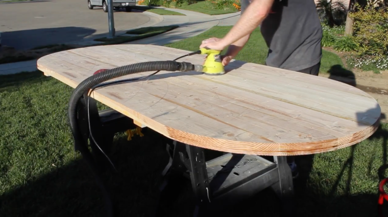 Sanding the table top with a random orbital sander