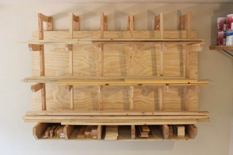 wall-mount lumber rack full of wood, boards and plywood