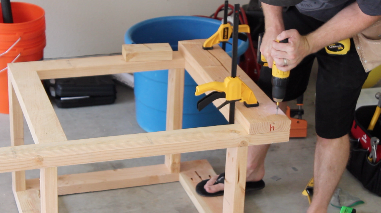 attaching 2 by 6 board to reinforce workbench leg