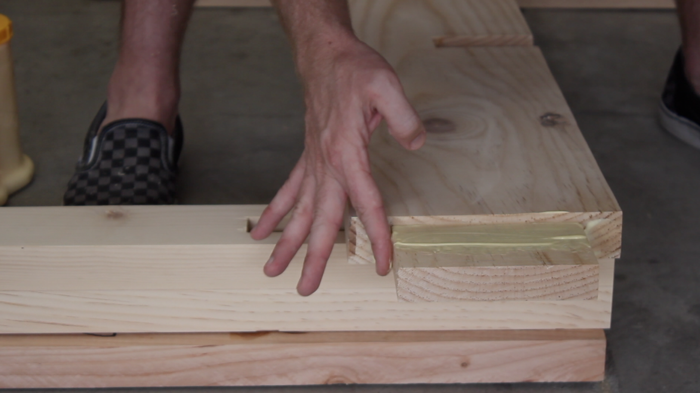 applying wood glue to through tenon on table stretcher