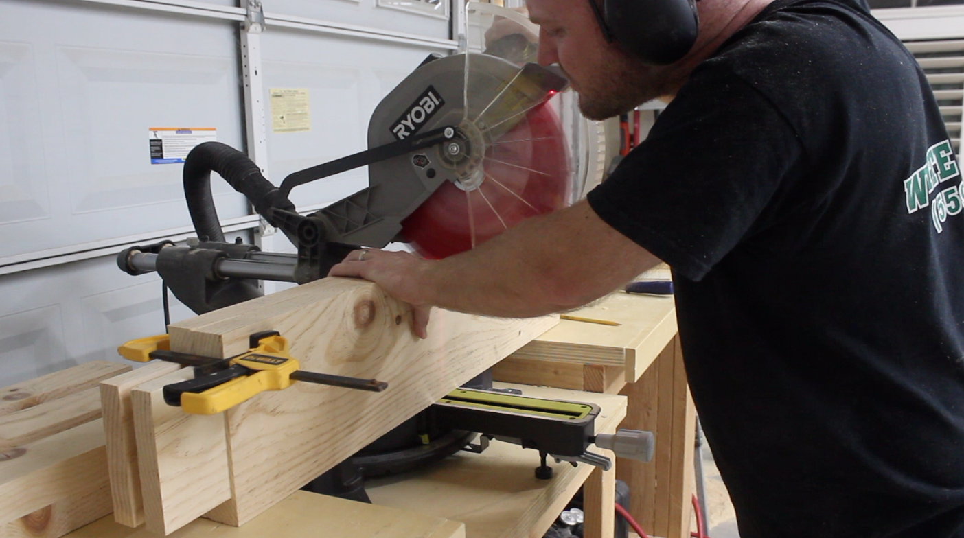 man using a miter saw to cut rabbets in table stretchers
